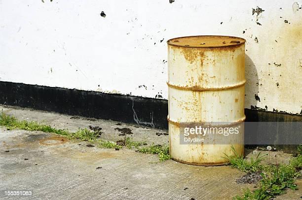 ラスティホワイトたドラム缶アゲインスト工場の壁