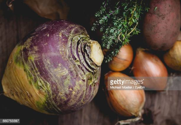 rutabaga and onions on table - rutabaga stock pictures, royalty-free photos & images
