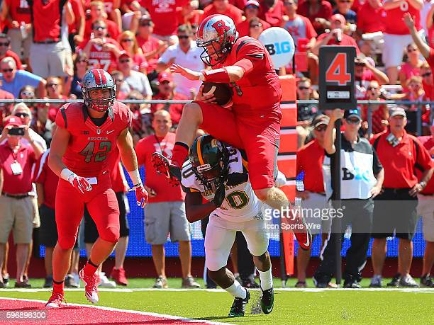 Rutgers Scarlet Knights quarterback Hayden Rettig hurdles over Norfolk State Spartans defensive back Sandy Chapman and scores atouchdown during the...