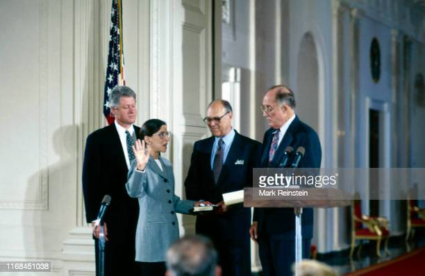 Ruth Bader Ginsburg holds her right hand up as Chief Justice William H Rehnquist administers the oath of office as she is sworn in as Associate...
