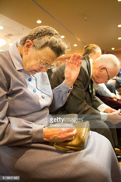 Ruth Douglas of Decatur Illinois prays before US Senator Ted Cruz speaks at a campaign rally for the candidate on March 14 2016 in Decatur Illinois...