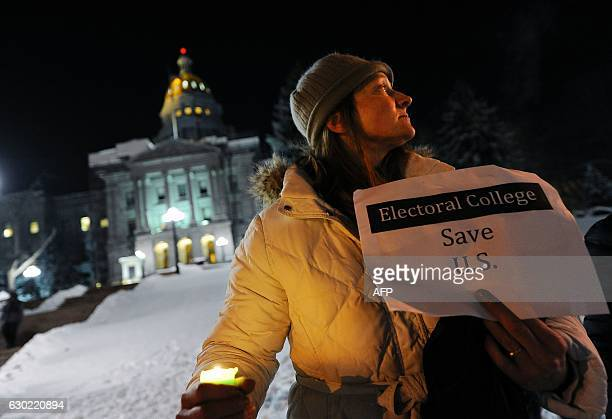 Ruth Fulton demonstrates during a candlelight vigil against US Presidentelect Donald Trump outside the Colorado Capitol building on the eve of the...