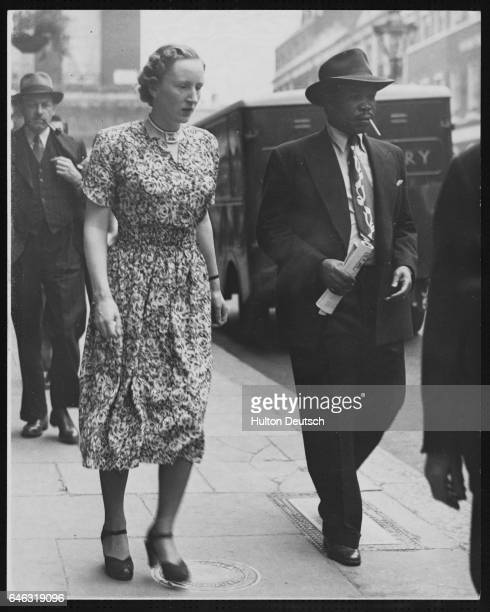 Ruth Khama and her husband, the banished Chief Designate of Bamangwato, Seretse, leave their Berkeley Square Hotel to go shopping during a visit to...