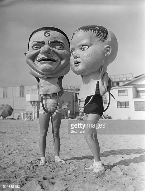 Ruth Lyon and Carmon Cook wear giant heads made of papiermache in Venice California on August 16 1935 They are part of the Mardi Gras celebrations...