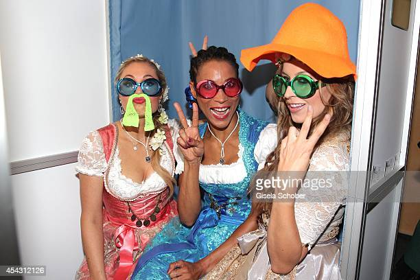 Ruth Moschner Annabelle Mandeng and Verena Kerth pose in a photo booth during the Dresscoded Hippie Wiesn 2014 at Golfclub Gut Thailing on August 28...