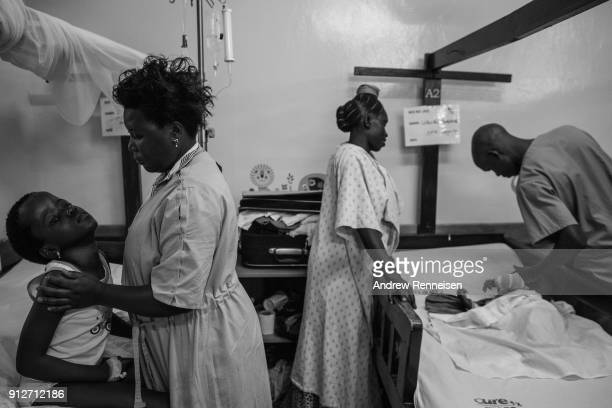 Ruth Nakitende supports her daughter Patricia Kirabo as they weight for a nurse to make his rounds at Cure Hospital on February 4 2017 in Mbale...