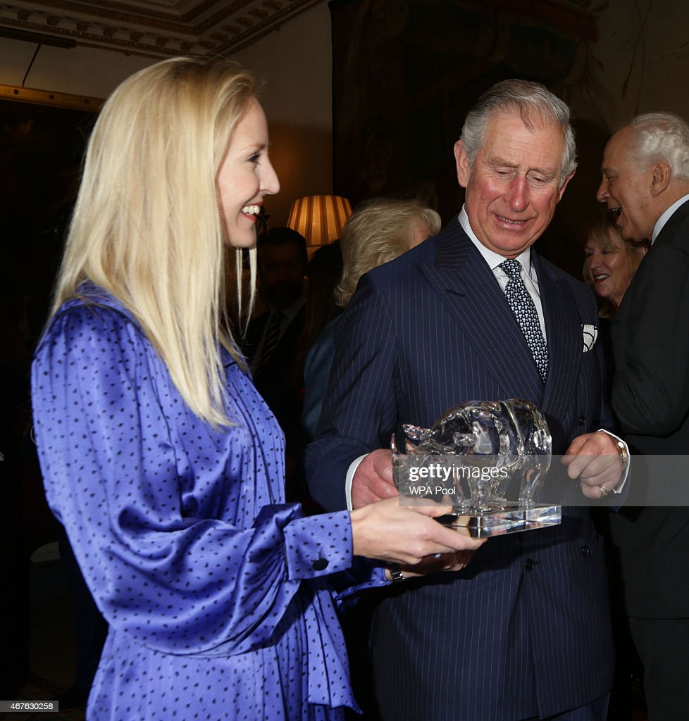 Ruth Powys, Chief Executive, Elephant Family, presents Prince Charles, Prince of Wales with a rhinoceros sculpture, The Perfect World Foundation's award for Conservationist of the Year 2014, for Mark Shand and the Elephant Family, during a reception to launch 'Travels To My Elephant' at Clarence House on March 26, 2015 in London, England. In November 2015 a fleet of thirty rickshaws will journey 500km across Madhya Pradesh, India, in a race to save Asias elephants from extinction.