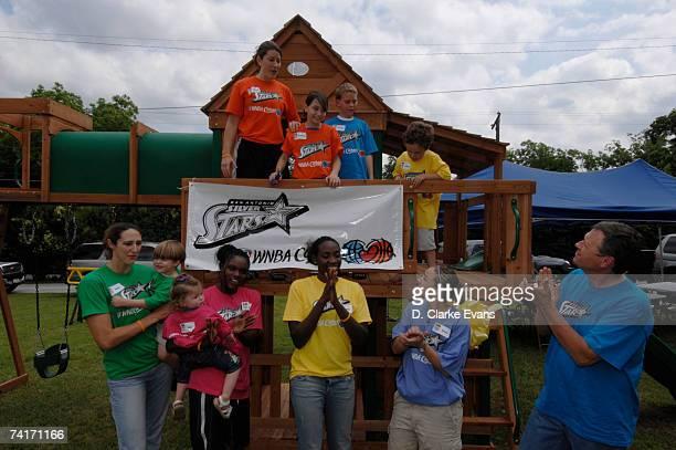 Ruth Riley Marie FerdinandHarris Shanna Crossley Sophia Young Becky Hammon and Head Coach Dan Hughes of of the San Antonio Silver Stars help build a...