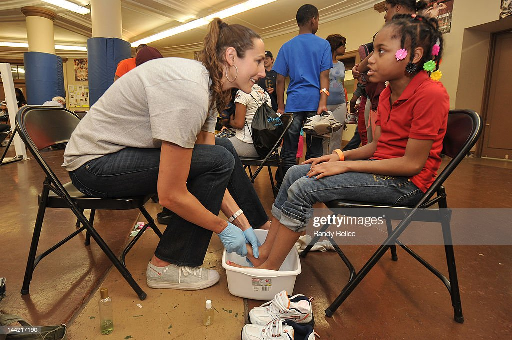 Ruth Riley of the Chicago Sky washes the feet of a recipient during the Samaritan Feet Shoe Distribution on May 11, 2012 at LaFollette Park Field House in the North Austin Community of Chicago, Illinois. The Chicago Sky and its Legacy Partner Samaritan Feet distributed more than 1000 pairs of new athletic and socks to pre-identified children as part its SKY Cares community outreach in partnership with WNBA Cares.