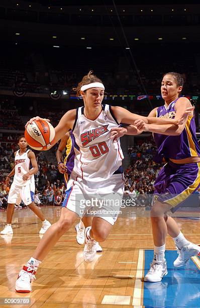 Ruth Riley of the Detroit Shock drives past Christi Thomas of the Los Angeles Sparks during their game at the Palace of Auburn Hills May 29 2004 in...