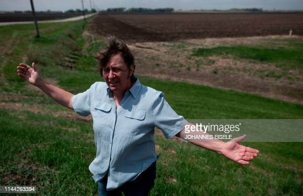 Ruth wife of farmer Sid Ready gestures as she stands on the ditch which hold most of the flood water away from their farm near Scribner Nebraska on...
