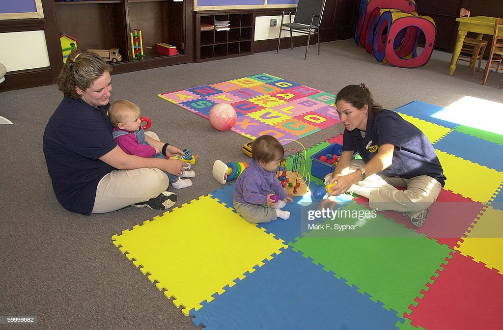 Ruthcarol Touhey (left) and Katie Paun play with youngsters in the daycare center at Results Gym.
