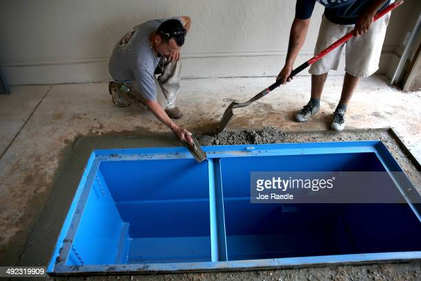 Rutilio Munoz and Jose Zermeño install a Storm Safe Shelter tornado shelter in the floor of a garage as the town continues to recover from the...