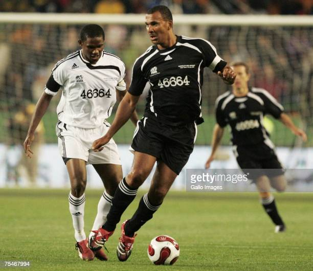 Ruud Gullit shields the ball from Samual Eto'o during the 90 Minutes for Mandela match between an Africa XI and a Rest of the World XI held at...