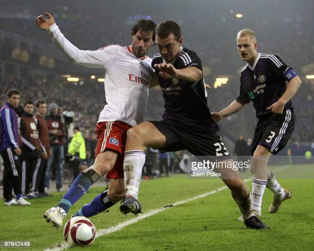 Ruud van Nistelrooy of Hamburg and Roland Juhasz of Anderlecht battle for the ball during the UEFA Europa League round of 16 first leg match between...