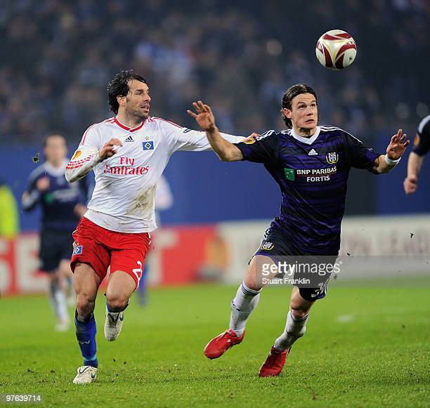 Ruud van Nistelrooy of Hamburg is challenged by Guillaume Gillet of Anderlecht during the UEFA Europa League round of 16 first leg match between...