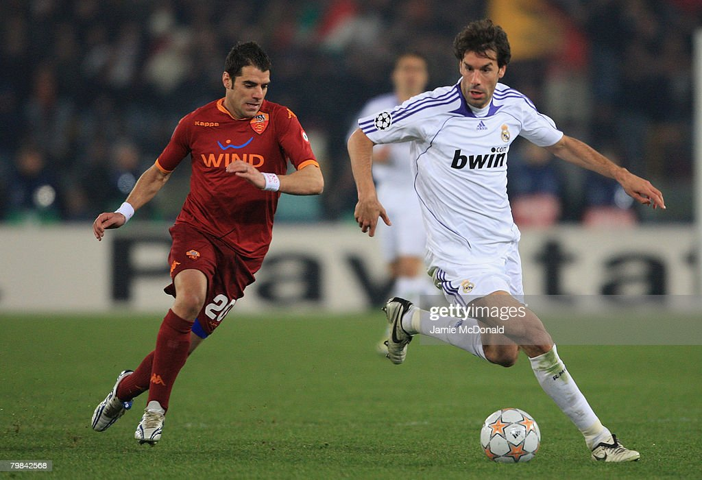 Ruud Van Nistelrooy of Madrid is chased by Simone Perrotta of Roma during the UEFA Champions League first knockout round, first leg match between AS Roma and Real Madrid at the Olympic Stadium on February 19, 2008 in Rome, Italy.