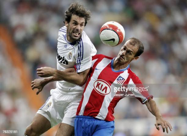 Ruud van Nistelrooy of Real Madrid duels for the ball with Mariano Pernia of Atletico de Madrid during the Spanish League match between Real Madrid...