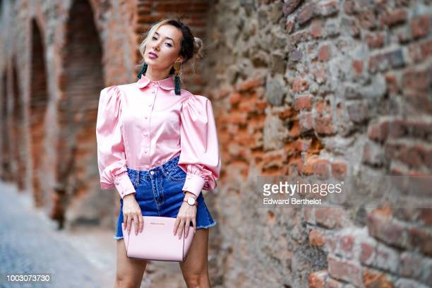 Ruxandra Chis wears a white dress with floral pink prints a silver bag during Feeric Fashion Week 2018 on July 21 2018 in Sibiu Romania