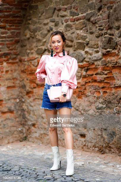 Ruxandra Chis wears a pink ruffled silky shirt blue denim shorts white boots a pink bag earrings on July 21 2018 in Sibiu Romania