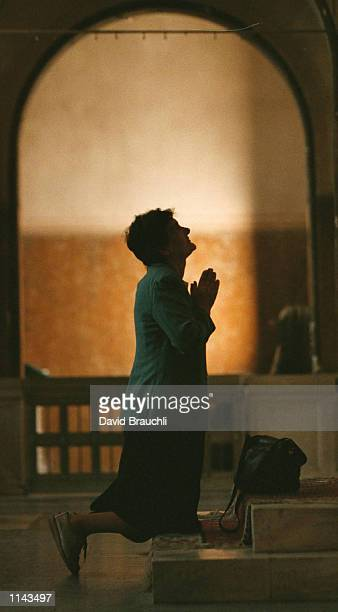 Ruza Batkovic prays during mass in a church on Sarajevo's Sniper Alley Sunday Oct. 8, 1995. Sarajevo citizens are looking forward to the return of...