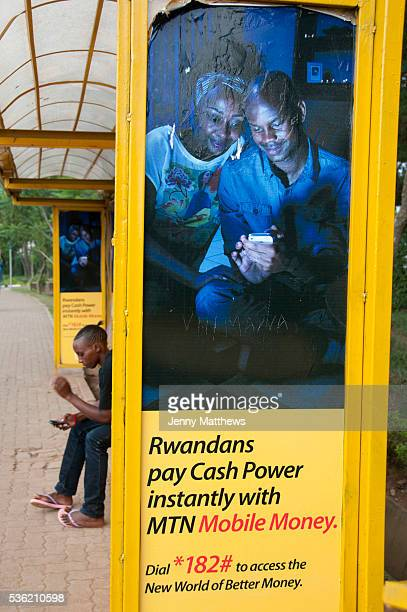 Rwanda February 2014 Kigali A young man looks at his phone whilst sitting waiting in a bus shelter which has adverts for a mobile phone company MTN...