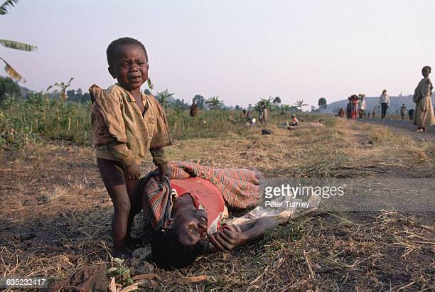 Rwandan boy cries over the dead body of his father, who has just died from cholera in a refugee camp in Zaire. Several minutes after this picture was...