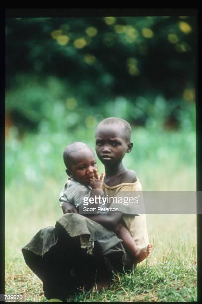 Rwandan children sit in the grass April 13 1994 in Kigali Rwanda Following the apparent assassination of Rwandan President Juvenal Habyarimana a...