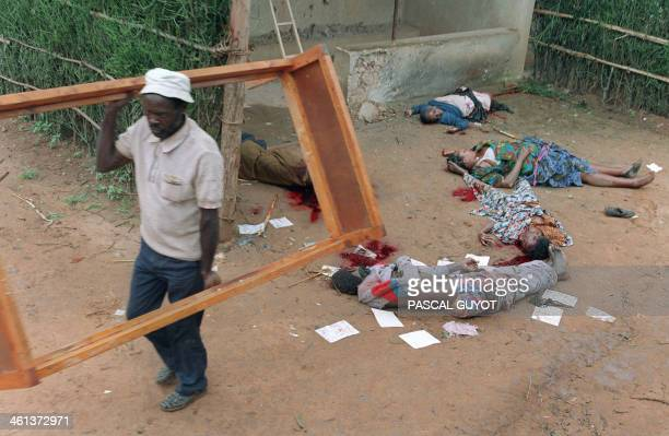 A Rwandan looter carries a bed frame out of a house of which inhabitants were killed following the Tutsi and Hutus massacres in Kigali on April 11...