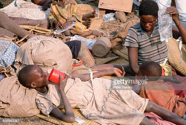 A Rwandan man cares for one of the thousands of refugees who fled the war in Rwanda and then fell victim to a cholera epidemic in a refugee camp in...