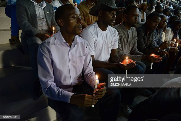 Rwandan men hold candles during a night vigil and prayer for genocide victims at the Amahoro stadium in Kigali Rwanda on April 7 2014 Solemn...