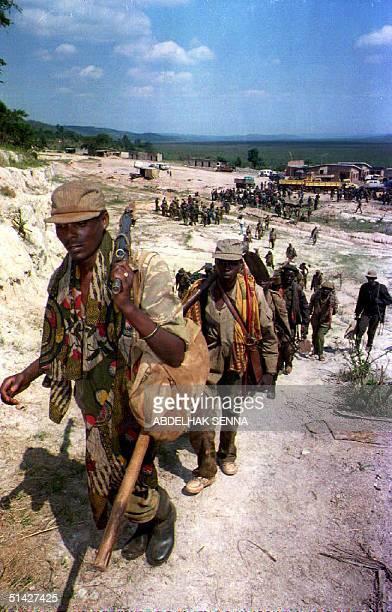 Rwandan Patriotic Front members carry weapons and ammunition on the Giterama frontline near Nyanza Rwanda 02 June 1994 Rwandan government forces have...