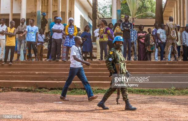 Rwandan peacekeeper of the United Nations Multidimensional Integrated Stabilization Mission in the Central African Republic patrols with an AK-47 as...