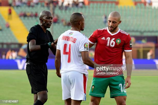 Rwandan referee Louis Hakizimana speaks with Namibia's defender Riaan Hanamub and Morocco's forward Nordin Amrabat during the 2019 Africa Cup of...