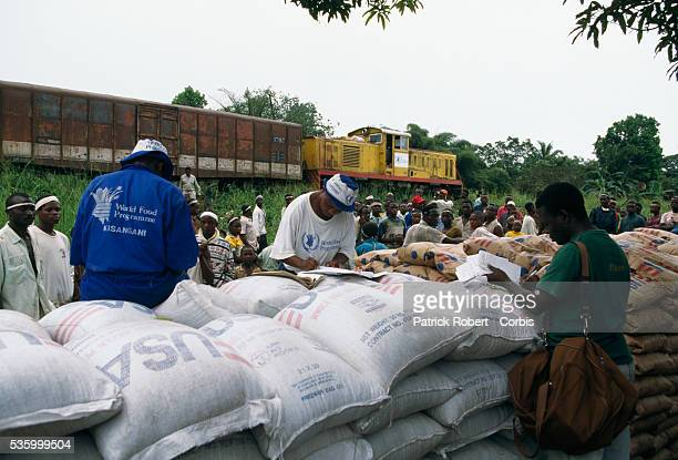 Rwandan refugees fleeing from the rebel army receive food that a train dropped off from the United Nations World Food Programme in Zaire on March 27...