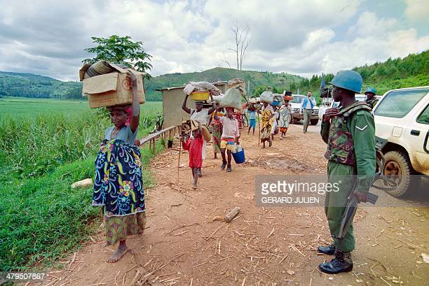 Rwandan refugees walk on the Byumba road as they flee from Kigali on May 11 1994 Rwanda's civil war continues after Hutu president Juvenal...