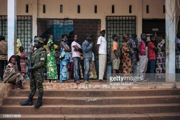 Rwandan soldier looks on as as voters queue to vote at the Barthélemy Boganda high school polling station in the 1st district in Bangui, Central...
