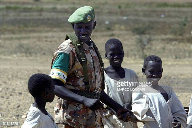 Rwandan soldier operating under the Africa Union mandate plays 02 November 2004 with children outside the AU base in Kab Kabiya north west of...