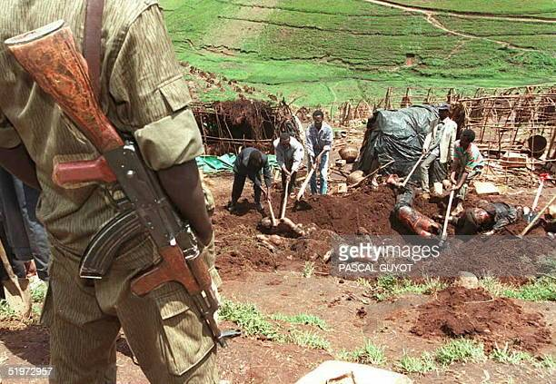 Rwandan soldier stands guard as bodies are exhumed from a mass grave at the Kibeho refugee camp 27 April to count the dead following the massacre of...