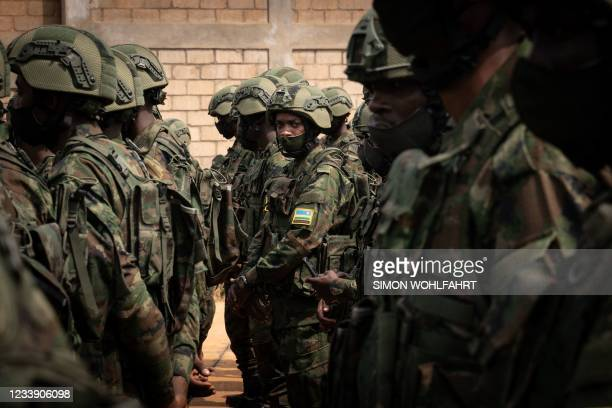 """Rwandan soldiers from Rwanda Defence Forces and Rwandan policemen prepare to board a """"Rwandair"""" plane for a military mission to Mozambique at Kanombe..."""