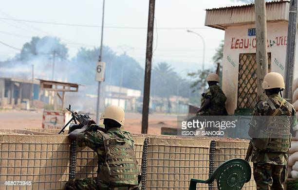Rwandan soliders of the MISCA look at a house burning on February 9 2014 in the 5th district of Bangui where a man was killed and burned the night...