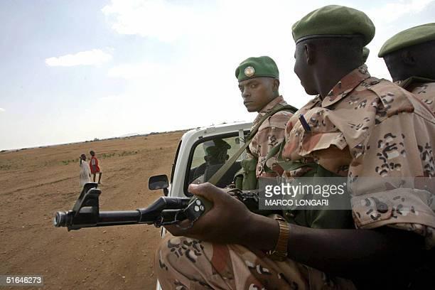 Rwandan troops operating under the Africa Union mandate patrol 02 November 2004 outside the AU base in Kab Kabiya north west of ElFasher Sudan 196...