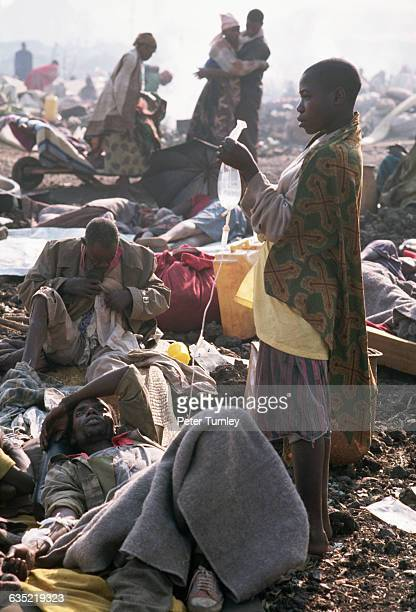 A Rwandan woman cares for one of the thousands of refugees who fled the war in Rwanda and then fell victim to a cholera epidemic in a refugee camp in...