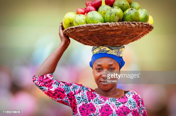 rwandan woman carrying basket full of fruits - african culture stock pictures, royalty-free photos & images