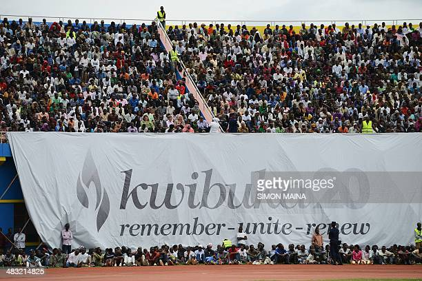 Rwandans gather under a banner reading in Kinyarwanda 'Kwibuka 20' at the Amahoro stadium in Kigali on April 7 during a ceremony marking the 20th...