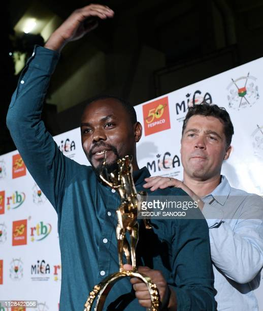 """Rwanda's film Director Joel Karekezi, winner of the 26th Pan-African Film and Television Festival for """"The mercy of the jungle"""", poses with his..."""