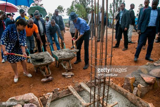 Rwanda's President Paul Kagame and Commonwealth Secretary General Patricia Janet Scotland pour concrete on a construction site of a secondary school...