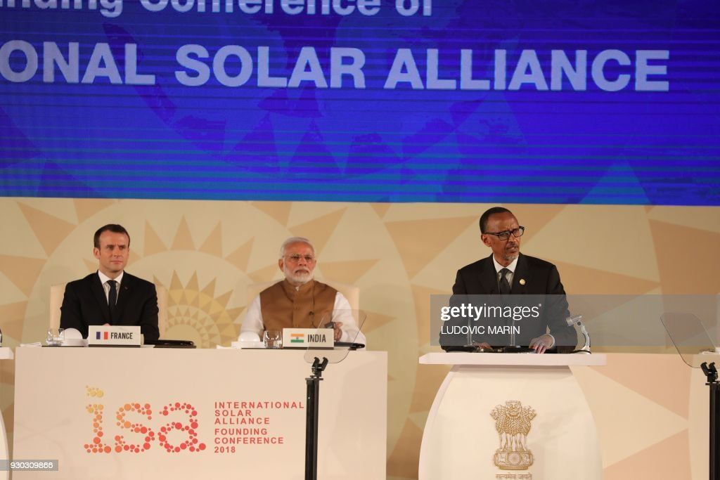Rwanda's President Paul Kagame delivers his speech next to French President Emmanuel Macron (L) and Indian Prime Minister Narendra Modi (C) during the founding conference of the International Solar Alliance in New Delhi on March 11, 2018. The International Solar Alliance (ISA) organizes more than 121 'sunshine' countries that are situated or have territory between the Tropic of Cancer and the Tropic of Capricorn, with the aim of boosting solar energy output in an effort to reduce global dependence on fossil fuels. / AFP PHOTO / Ludovic MARIN
