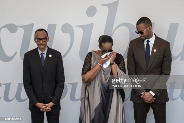 TOPSHOT Rwanda's President Paul Kagame his wife Jeanette and his son Ivan react in front of a wreath for the 25th Commemoration of the 1994 Genocide...