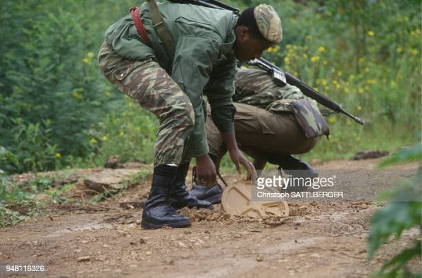 Rwandese government soldiers demining a road
